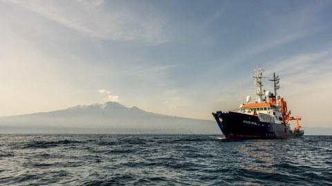 Das Forschungsschiff POSEIDON vor dem Vulkan Ätna, aufgenommen während der Ausfahrt POS496 (Quelle: Felix Gross)..